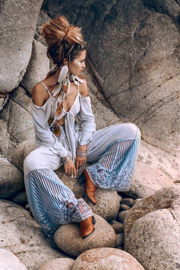 Giovane donna alla moda seduta sulla spiaggia di pietra fotografia stock