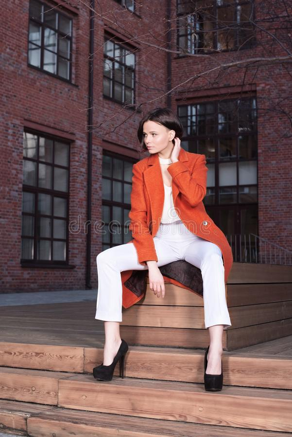 Giovane donna alla moda in un cappotto rosso e nei pantaloni bianchi che si siedono sulle scale di legno immagini stock