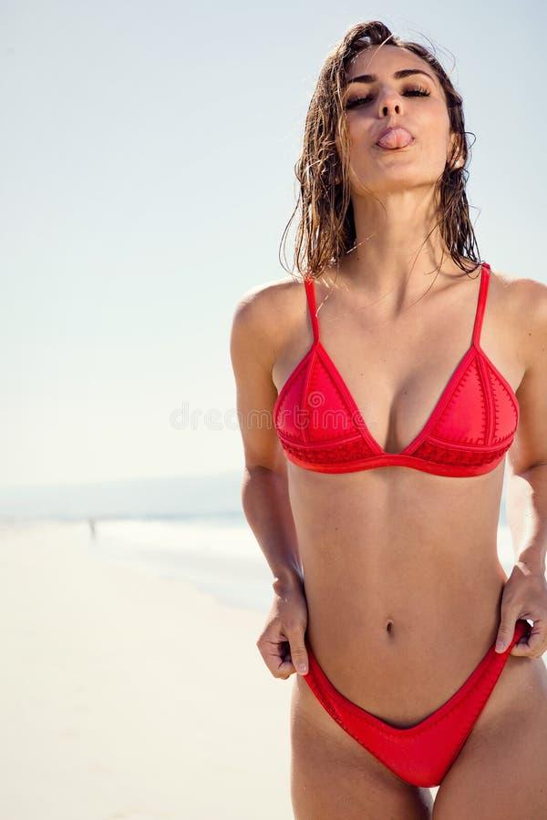 Giovane donna alla spiaggia che attacca fuori lingua immagini stock libere da diritti