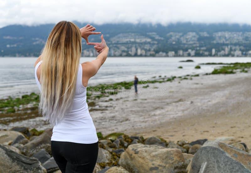 Giovane donna alla spiaggia di Stanley Park che esamina Vancouver dentro immagine stock