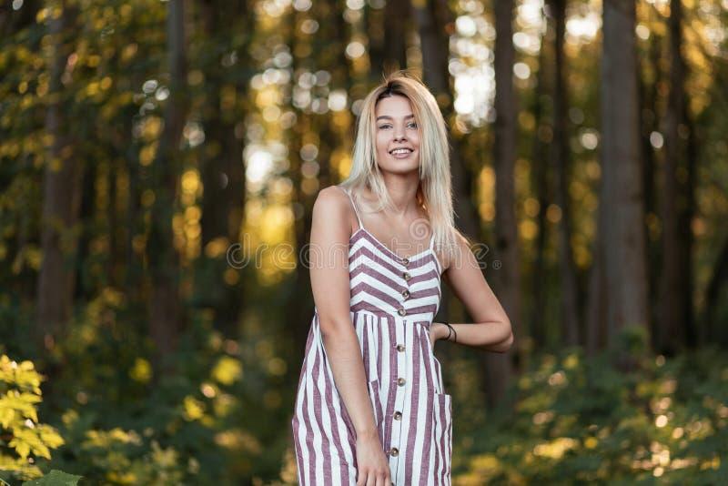 Giovane donna allegra alla moda con un bello sorriso in una condizione a strisce rosa d'avanguardia del vestito nella foresta un  fotografie stock