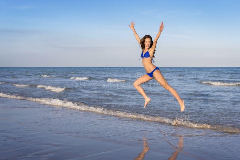 Giovane donna allegra in bikini che salta sulla spiaggia fotografia stock libera da diritti