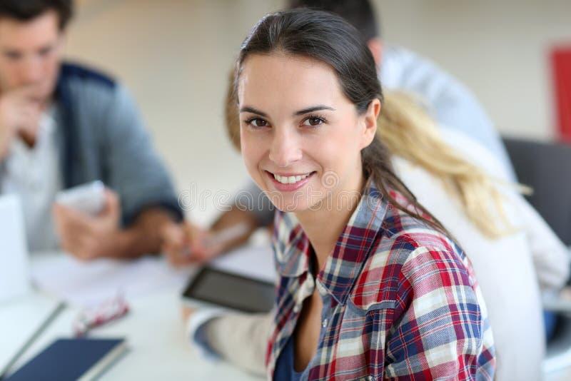 Giovane donna allegra che assiste alla classe con i compagni di scuola fotografie stock
