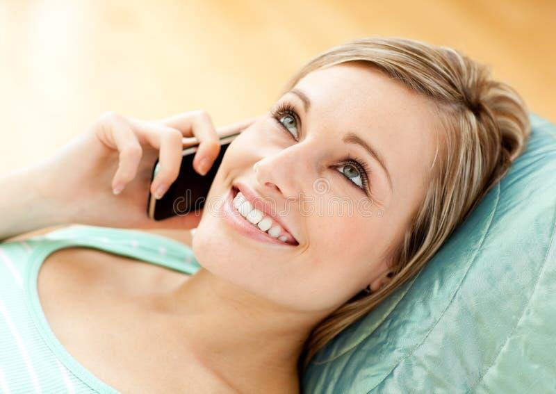 Giovane donna allegra che comunica sul telefono che si trova su un sofà fotografie stock