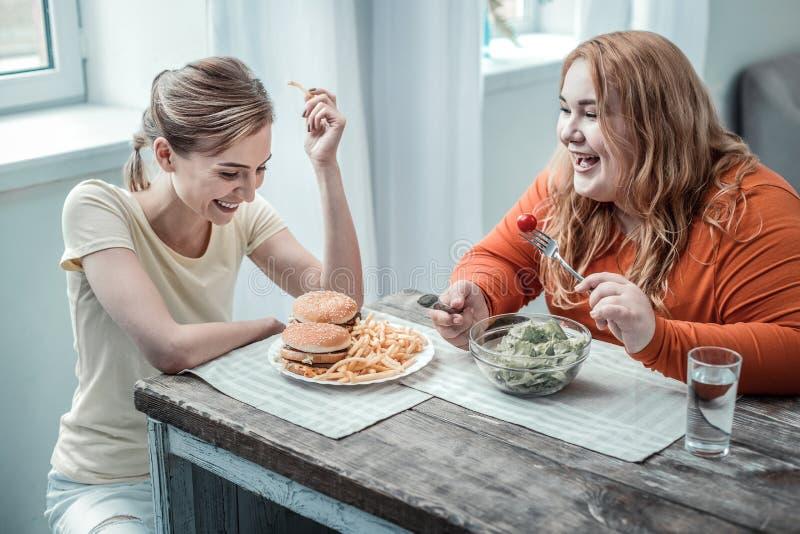 Giovane donna allegra che esamina piatto con gli hamburger immagini stock libere da diritti