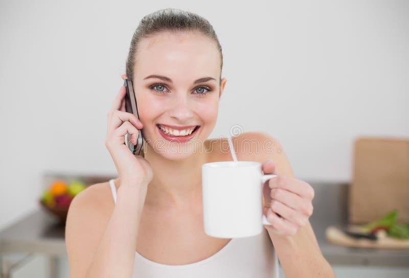 Giovane donna allegra che fa una telefonata e che tiene una tazza che esamina macchina fotografica immagini stock