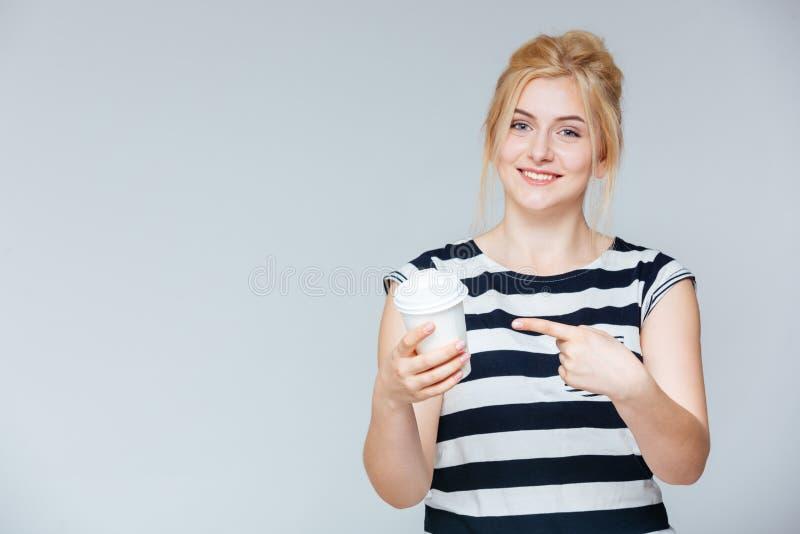 Giovane donna allegra che indica sulla tazza affinchè coffe vadano fotografia stock libera da diritti