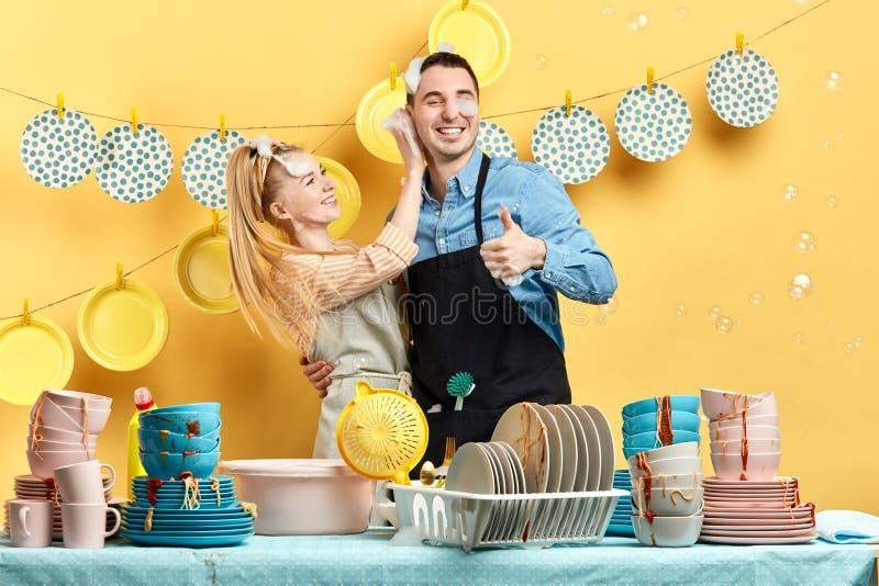 Giovane donna allegra che lava le orecchie del suo ragazzo con schiuma immagini stock