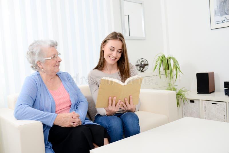Giovane donna allegra che legge un libro per la donna senior anziana a casa fotografia stock libera da diritti