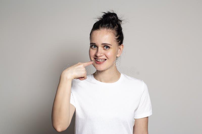 Giovane donna allegra che mostra i ganci sui suoi denti Isolato su priorit? bassa bianca fotografia stock libera da diritti