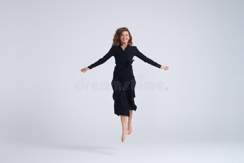 Giovane donna allegra che salta su nell'aria immagini stock