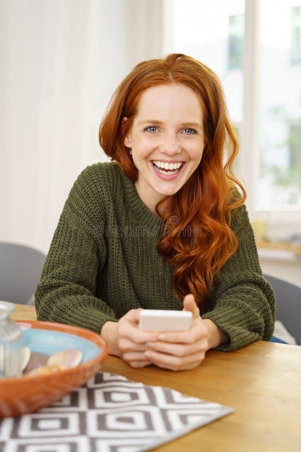 Giovane donna allegra che si siede alla tavola con il telefono immagine stock