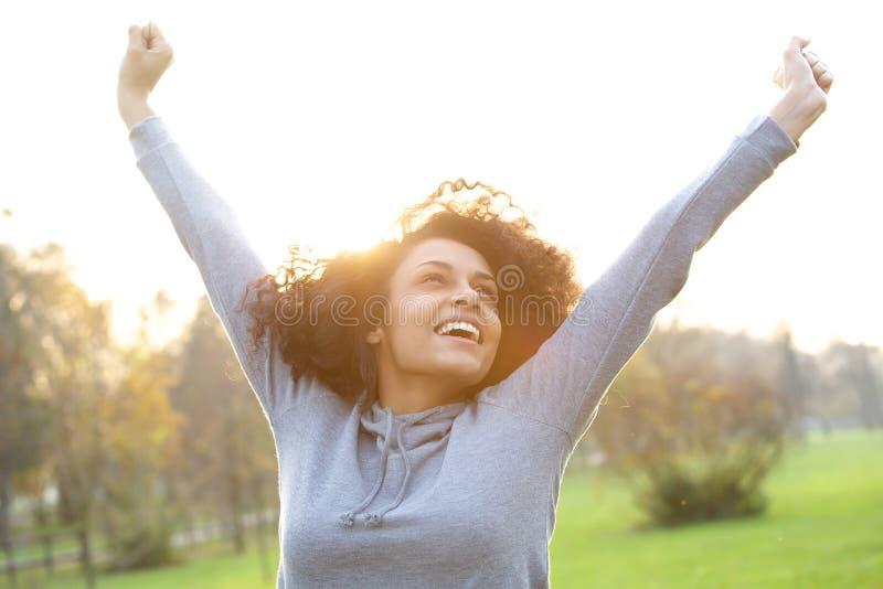 Giovane donna allegra che sorride con le armi alzate fotografia stock