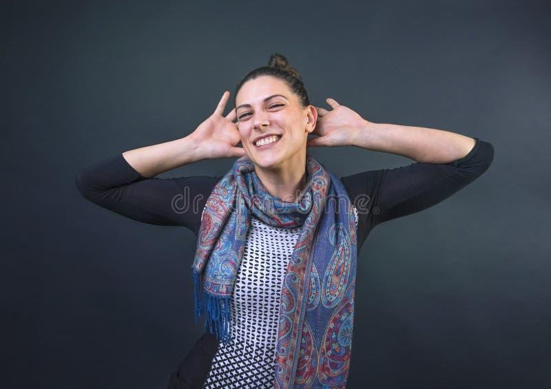 Giovane donna allegra che sorride nella macchina fotografica con le sue armi dietro la sua testa fotografia stock