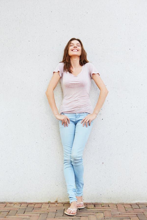 Giovane donna allegra che sta contro la parete e sorridere immagini stock
