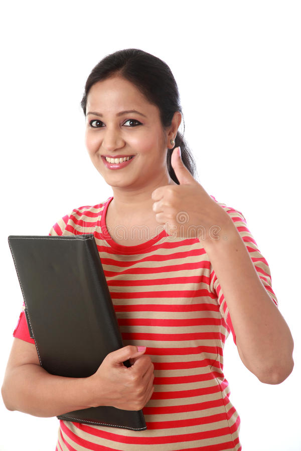 Giovane donna allegra che tiene una cartella e che compone pollice immagini stock libere da diritti
