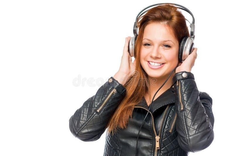 Giovane donna allegra con le cuffie in vestiti neri fotografia stock
