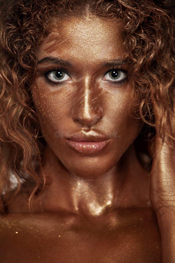 Giovane donna allegra con trucco di modo di arte Una donna stupefacente con oro e trucco selvaggio della pittura immagini stock