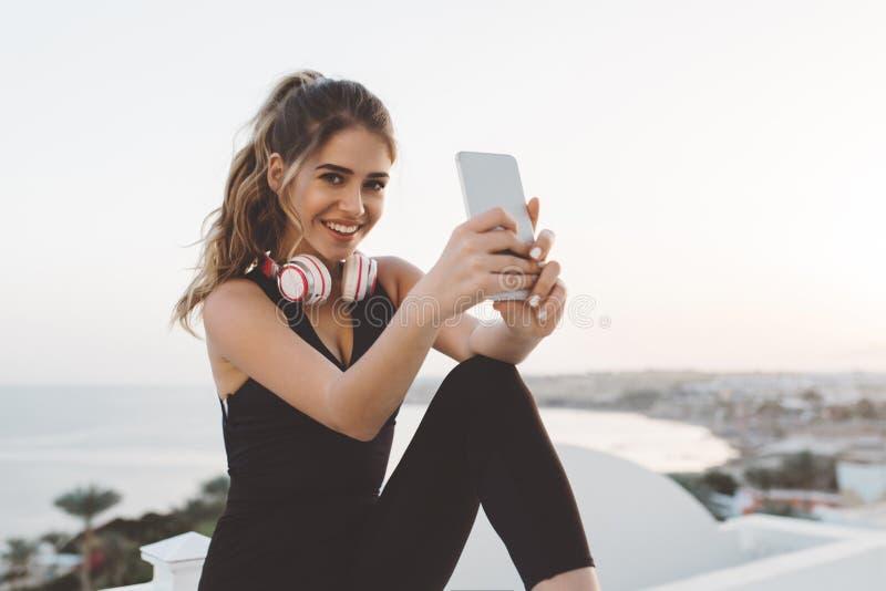 Giovane donna allegra felice in abiti sportivi attraenti che fanno selfie sul telefono, sorridendo alla macchina fotografica, god fotografia stock libera da diritti