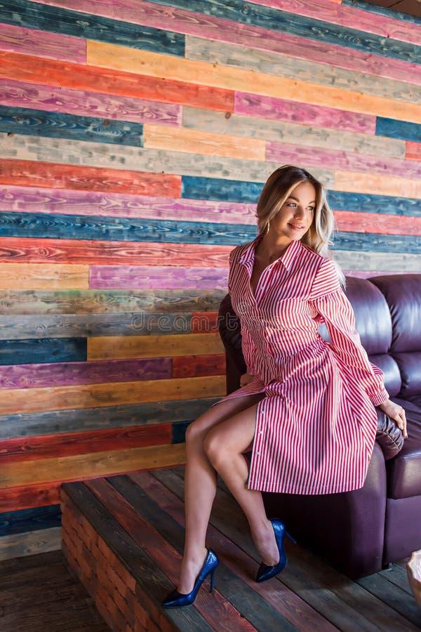 Giovane donna allegra felice che porta il suo vestito rosa che guarda da parte con il sorriso allegro e affascinante rilassamento fotografie stock libere da diritti