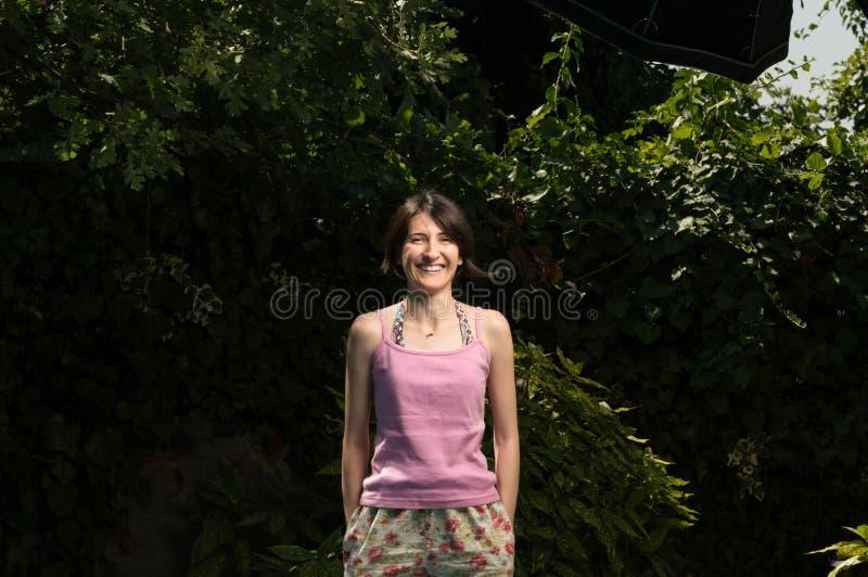 Giovane donna allegra felice che sta nel giardino fotografie stock libere da diritti