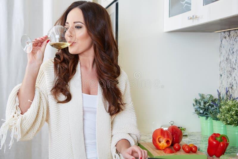 Giovane donna allegra in grembiule sulla cucina moderna immagini stock libere da diritti