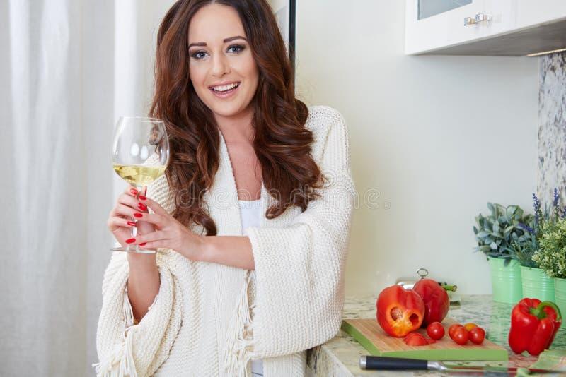 Giovane donna allegra in grembiule sulla cucina moderna fotografia stock
