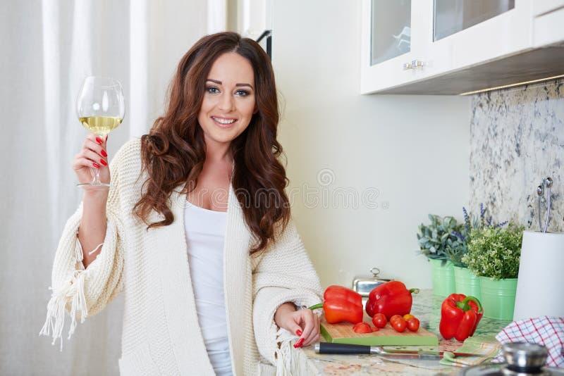 Giovane donna allegra in grembiule sulla cucina moderna immagine stock libera da diritti