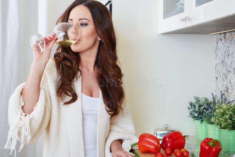Giovane donna allegra in grembiule sulla cucina moderna fotografie stock