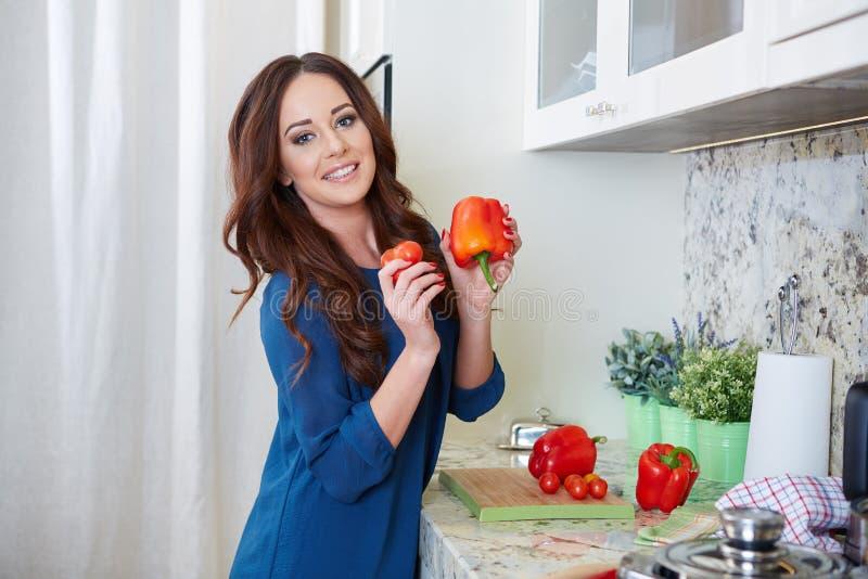 Giovane donna allegra in grembiule sulla cucina moderna immagini stock