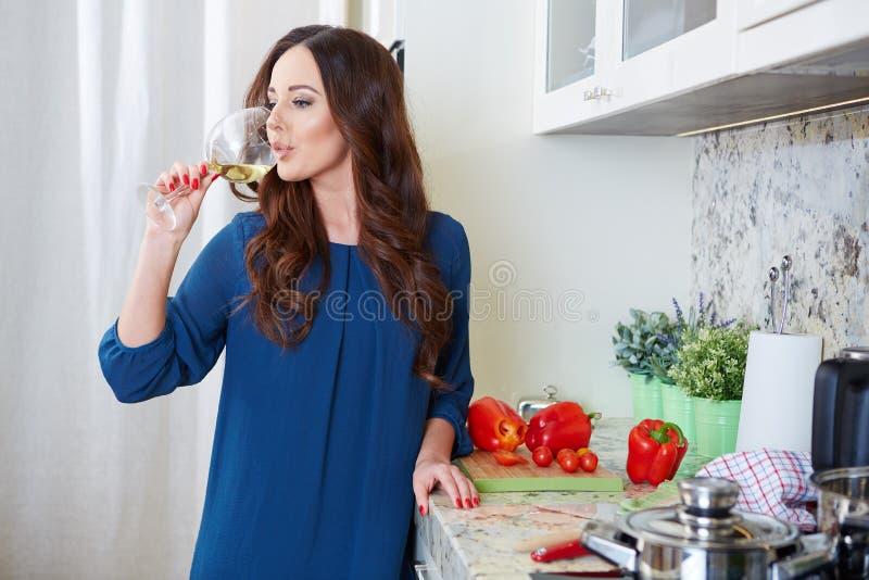 Giovane donna allegra in grembiule sulla cucina moderna immagine stock