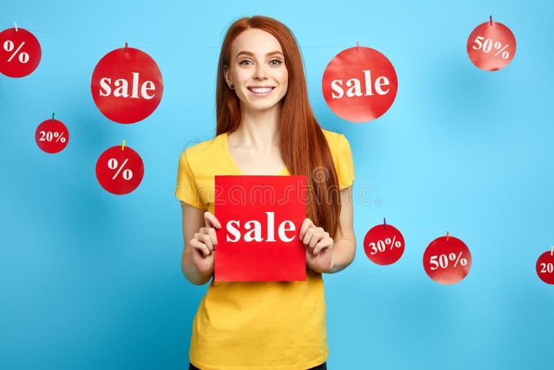 Giovane donna allegra in maglietta gialla alla moda che mostra un'automobile con la vendita di parola fotografia stock libera da diritti