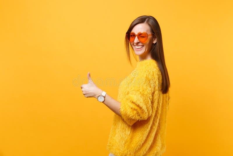 Giovane donna allegra in maglione della pelliccia e vetri arancio del cuore che guardano indietro, mostrando pollice su, lampeggi immagini stock