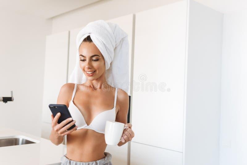 Giovane donna allegra in reggiseno ed asciugamano intorno alla sua testa fotografia stock