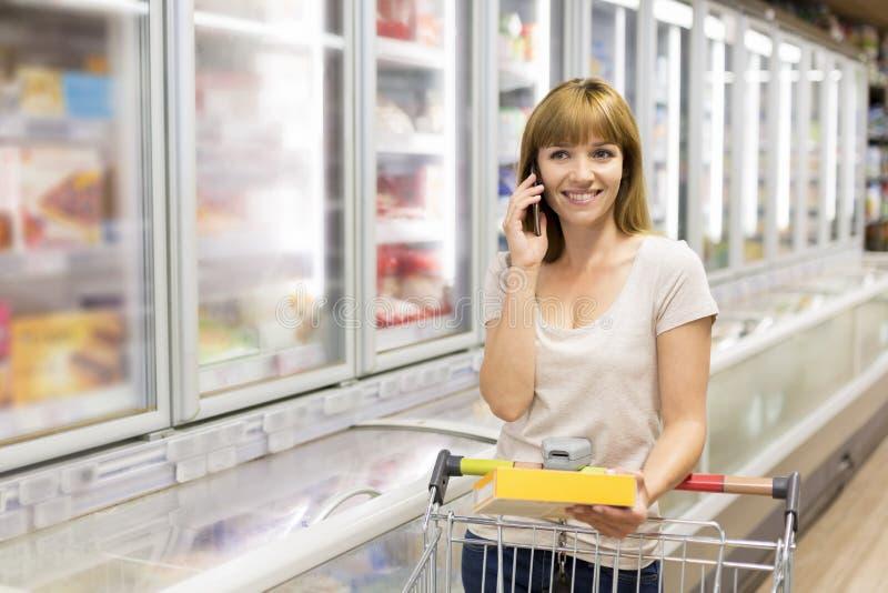 Giovane donna allegra sul telefono cellulare in supermercato fotografie stock libere da diritti
