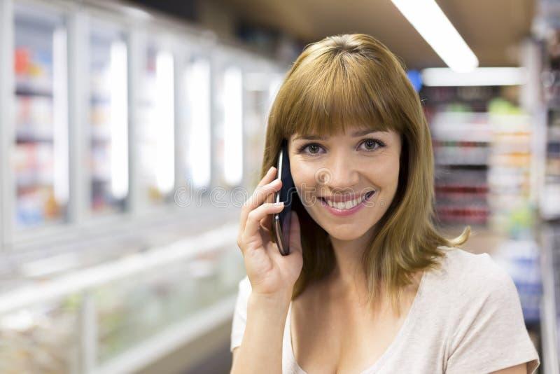 Giovane donna allegra sullo Smart Phone in supermercato sguardo della macchina fotografica fotografia stock