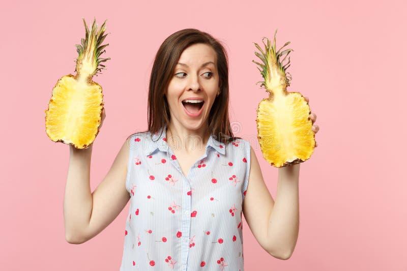 Giovane donna allegra in vestiti di estate che guardano da parte tenenti i halfs della frutta matura fresca dell'ananas isolata s immagine stock