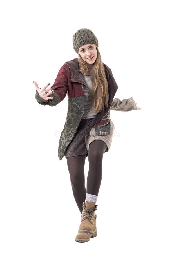 Giovane donna allegra in vestiti di inverno che portano beanie che balla e che gesticola fotografia stock libera da diritti