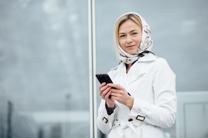 Giovane donna alta vicina di vista in una grande città facendo uso del telefono con la copia s immagini stock libere da diritti
