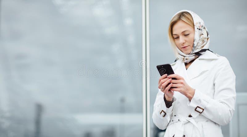 Giovane donna alta vicina di vista in una grande città facendo uso del telefono con la copia s fotografia stock