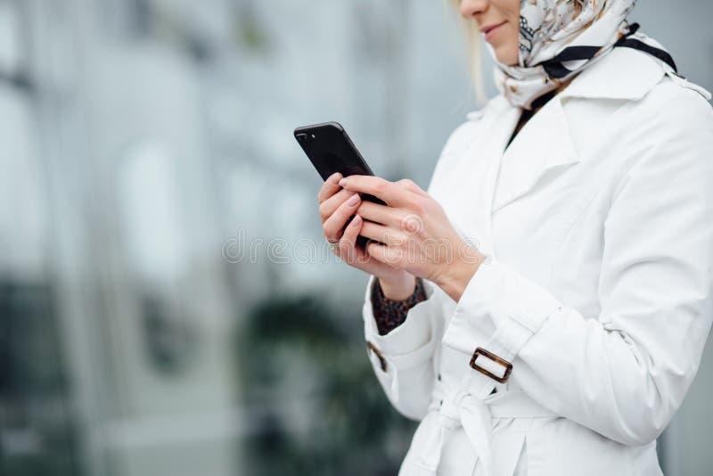 Giovane donna alta vicina di vista in una grande città facendo uso del telefono con la copia s fotografie stock
