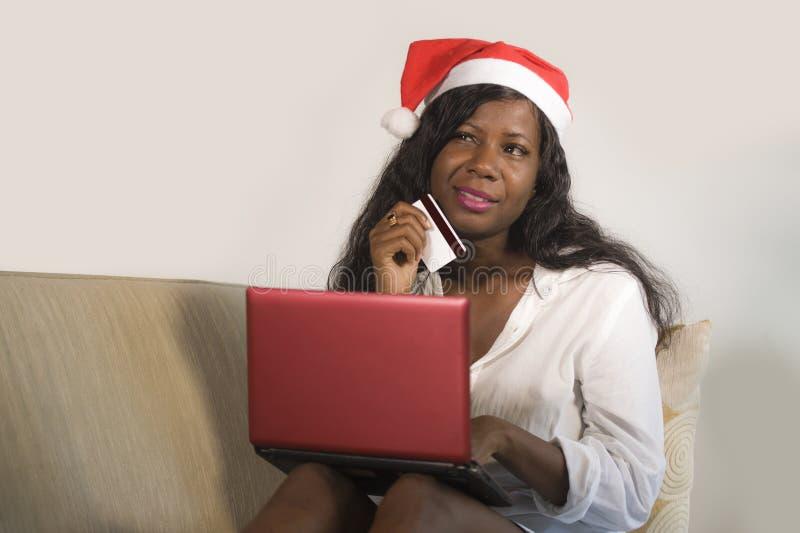 Giovane donna americana dell'africano nero felice ed attraente in cappello di Santa Claus che tiene il regalo di Natale di acquis immagini stock libere da diritti