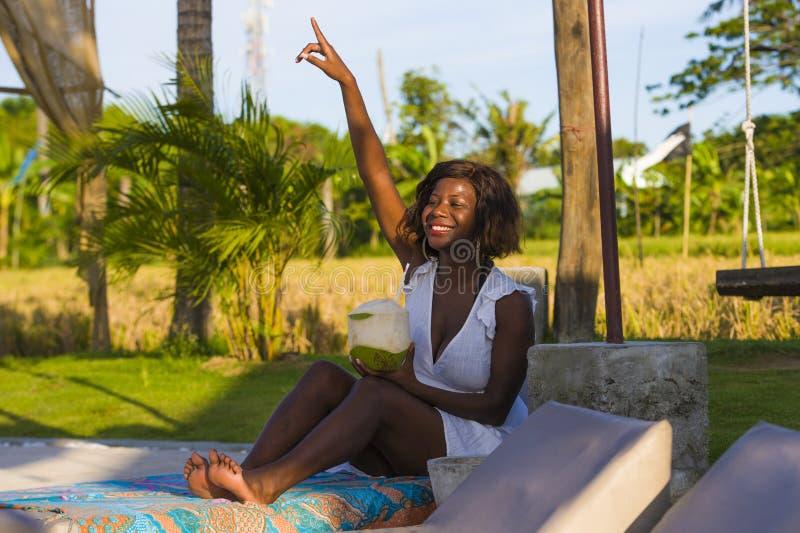 Giovane donna americana dell'africano nero felice ed attraente che si trova sull'amaca dello stagno alla stazione balneare tropic immagine stock libera da diritti