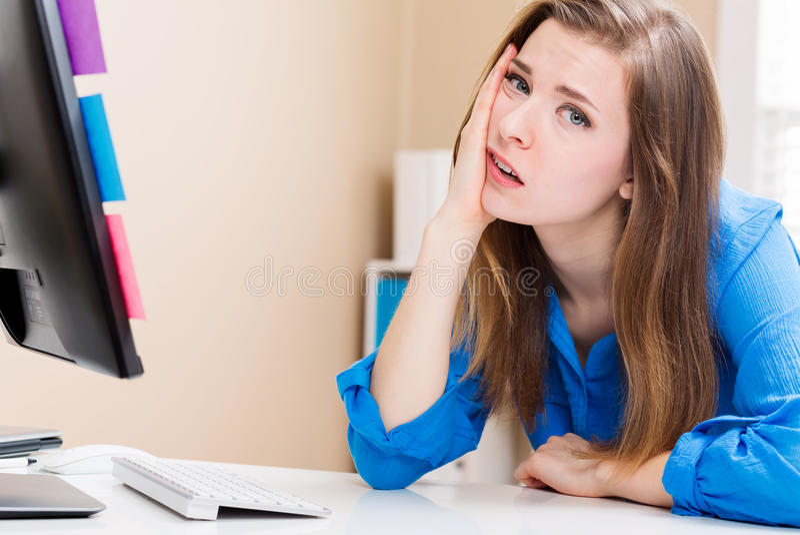 Giovane donna annoiata che si siede davanti al computer immagini stock