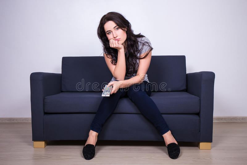 Giovane donna annoiata che si siede sul sofà e sulla TV di sorveglianza immagine stock