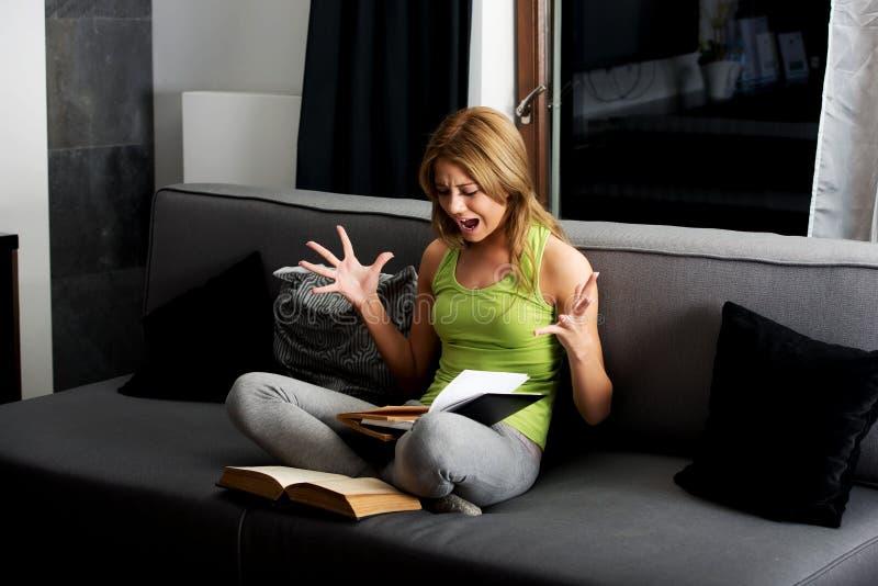 Giovane donna arrabbiata che impara all'esame su un sofà immagini stock libere da diritti