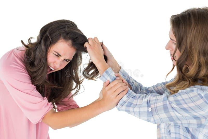 Giovane donna arrabbiata che tira i capelli delle femmine in una lotta fotografie stock libere da diritti