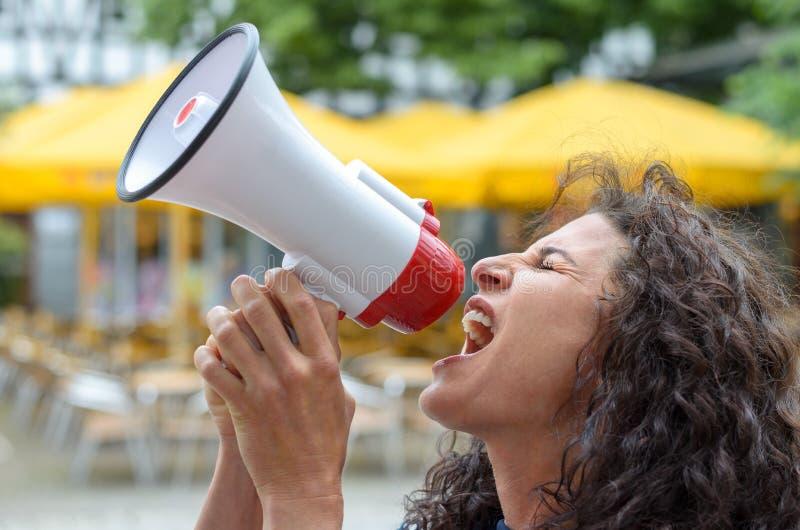 Giovane donna arrabbiata che usando un hailer rumoroso fotografia stock