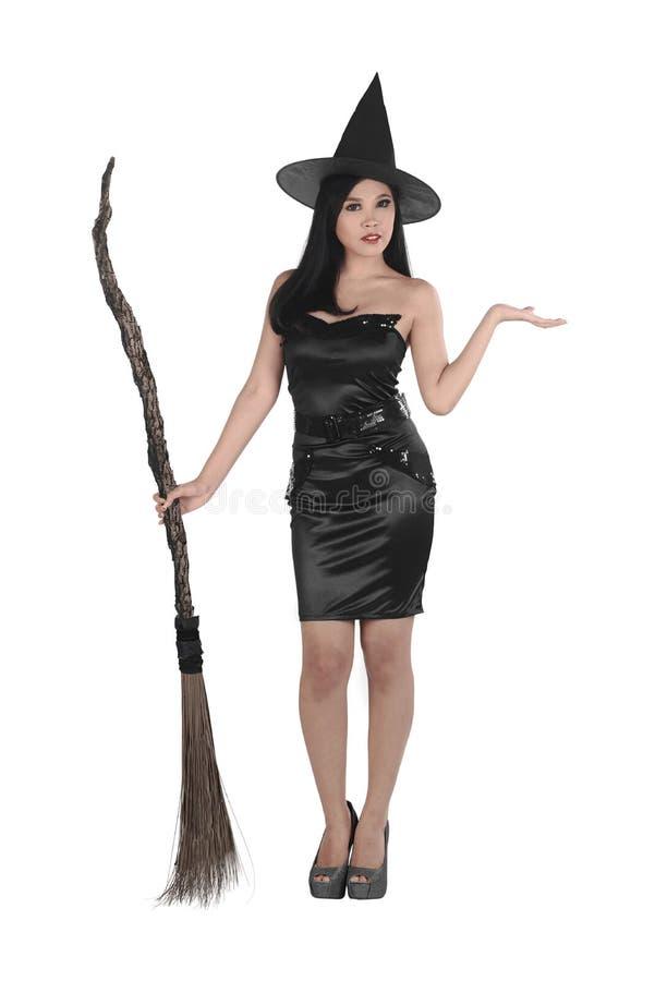 Giovane donna asiatica abbastanza sexy della strega con una scopa fotografia stock libera da diritti