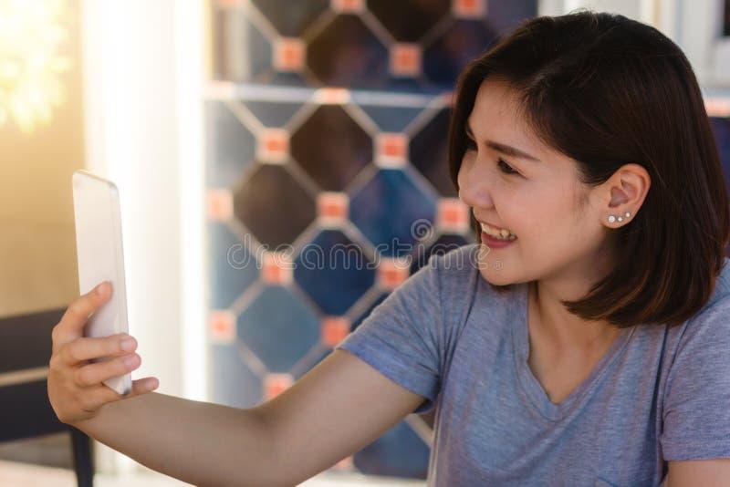 Giovane donna asiatica allegra che si siede in caffè facendo uso dello smartphone per la conversazione, la lettura e mandare un s fotografie stock libere da diritti